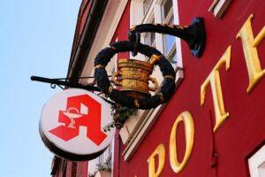 Das Bild zeigt ein Apothekenschild an einem roten Haus.